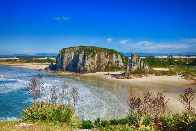 Praia da Guarita em Torres. Imagem composta por morros e praia.