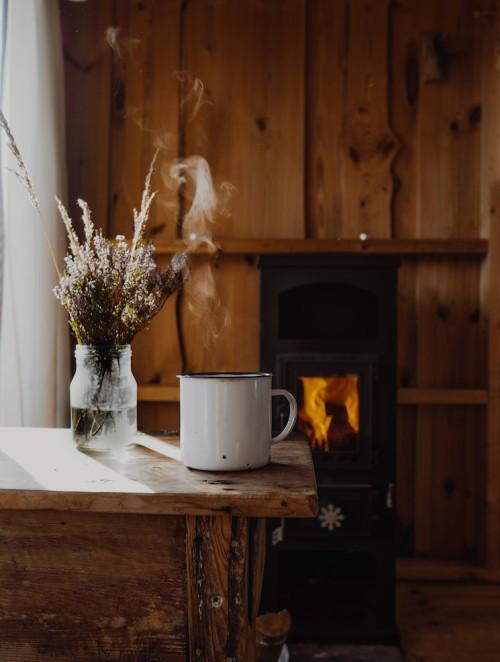 Ambiente com paredes e mesa de madeira, uma xícara de café em cima da mesa e um vaso de flores.