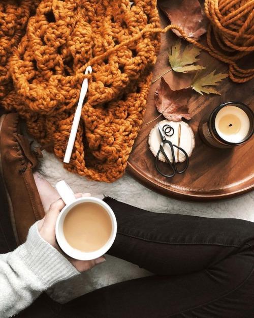 pessoa segurando uma xícara de café com uma mesa, folhas de outono e um crochê.